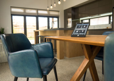 papamoa show home smart device controller on table with arm chair